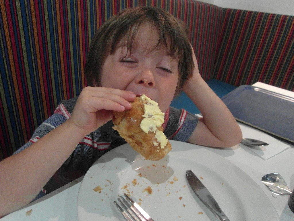 Boy eating a croissant with butter