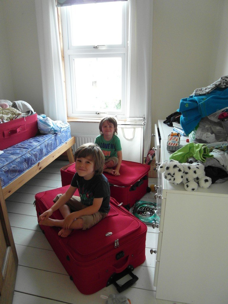 Two boys sitting on suitcases