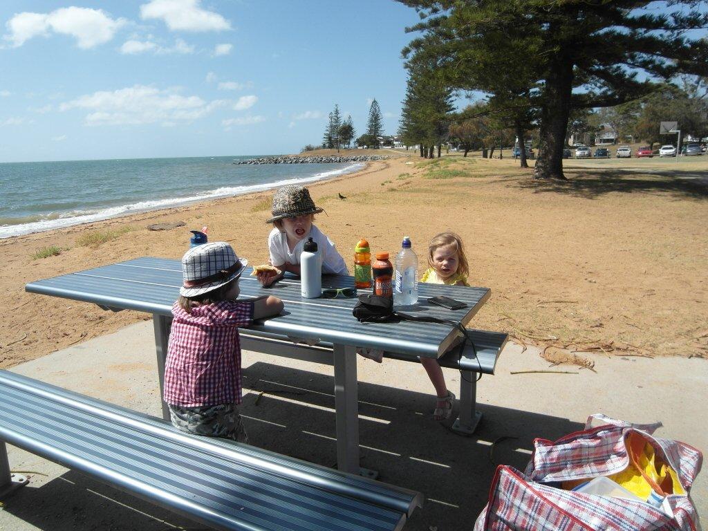 Children eating breakfast at the beach