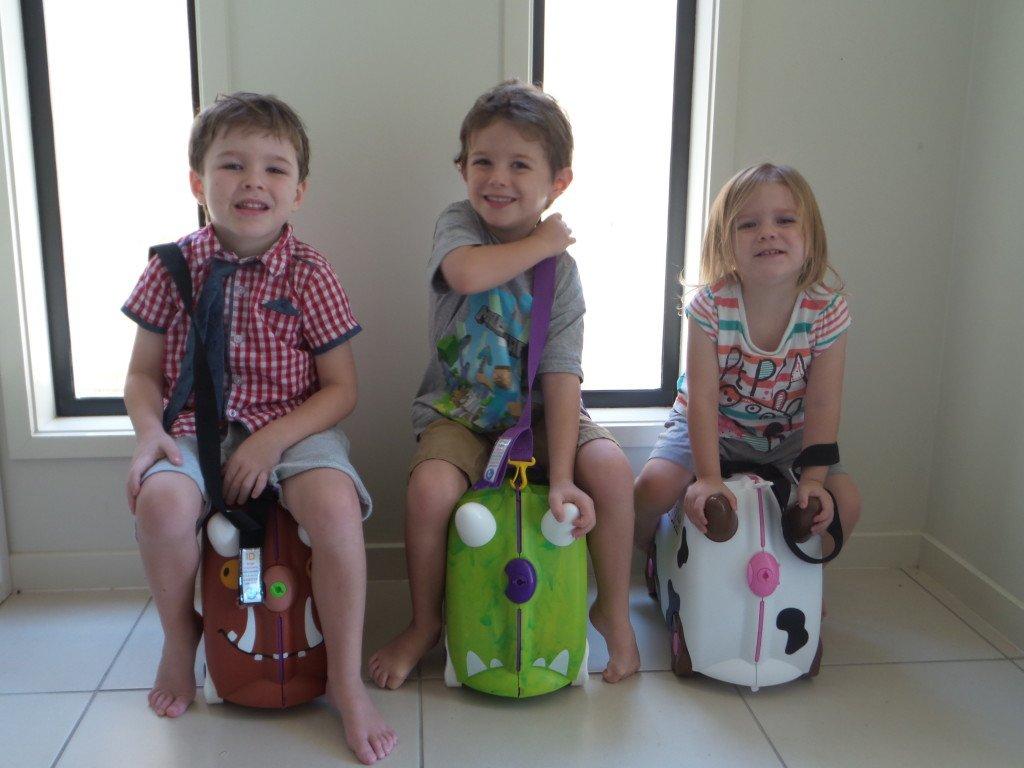 Three children sitting on their Trunki suitcases