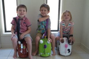 Three children sitting on their Trunki suitcases
