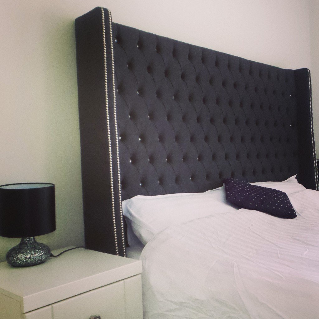 A bedroom with a winged headboard