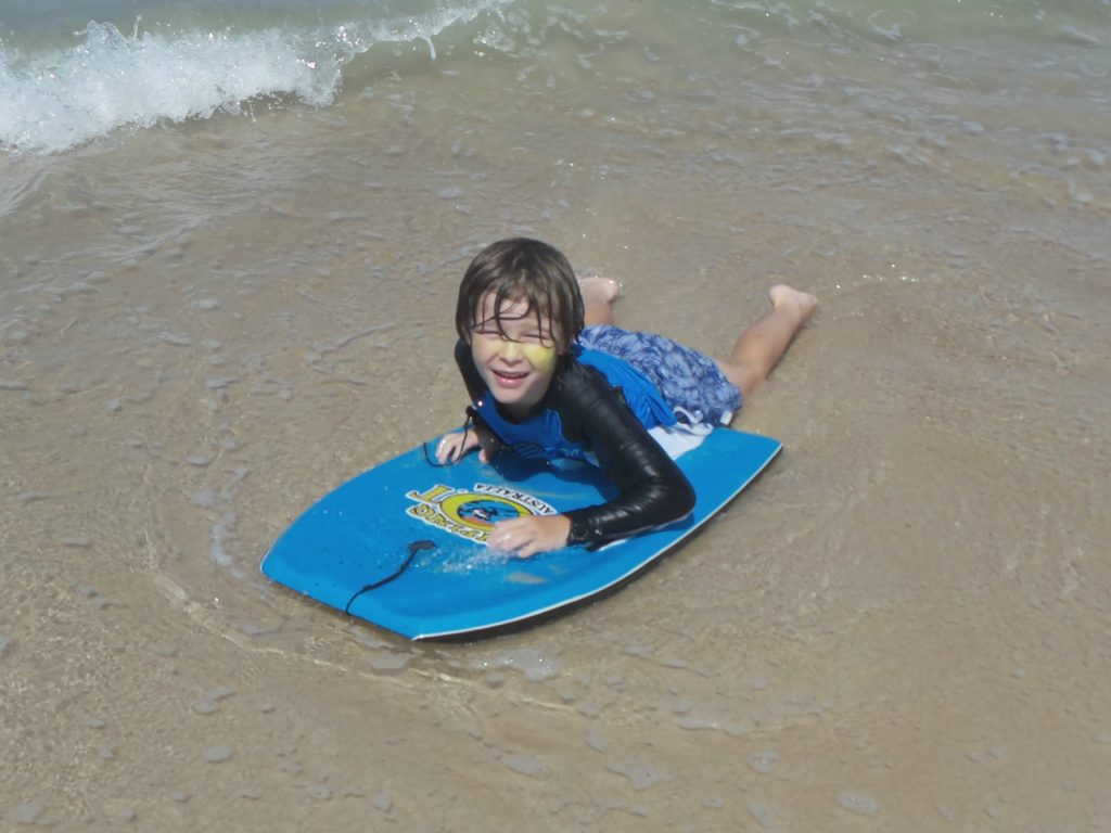 A boy on a body board on holiday